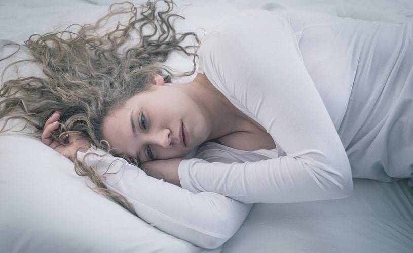 Depressed woman lying in bed is treated with Seroquel and SSRIs.
