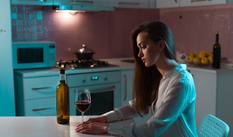 Woman with a bottle of wine drinking alone.