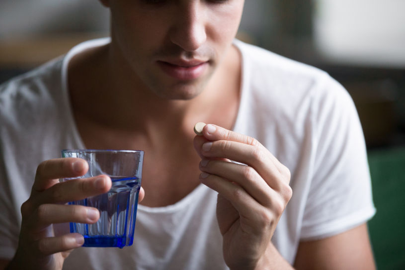 A man holds a glass of water in one hand and Demerol pill in another.