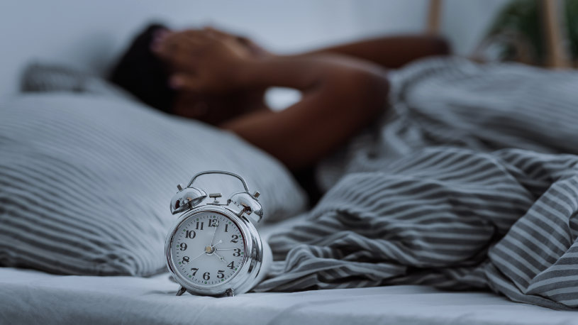 A man lying in bed experiences insomnia and can't fall asleep.