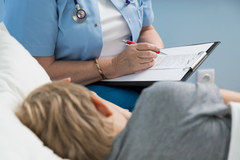A medical worker consults a patient lying in bed regarding Sonata abuse treatment options.