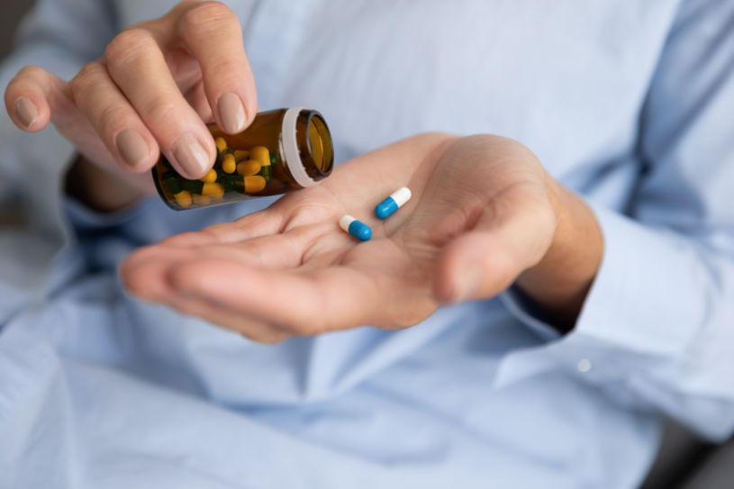 A woman holds Midazolam pills in her hand.