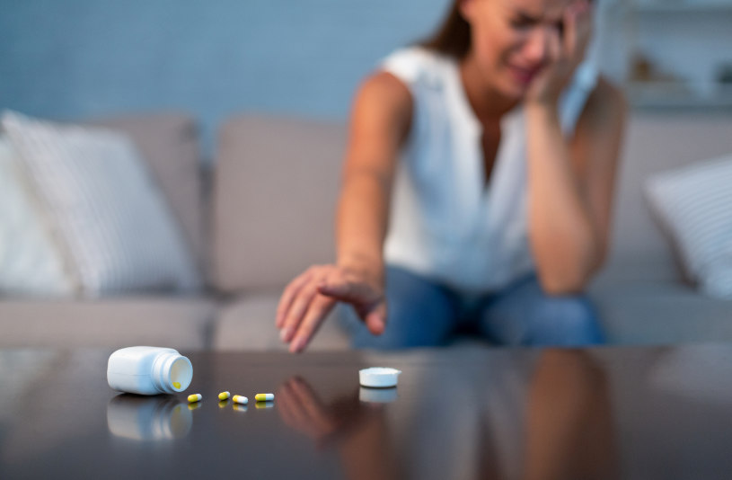 A woman in depression has dropped Viibryd pills on the table.