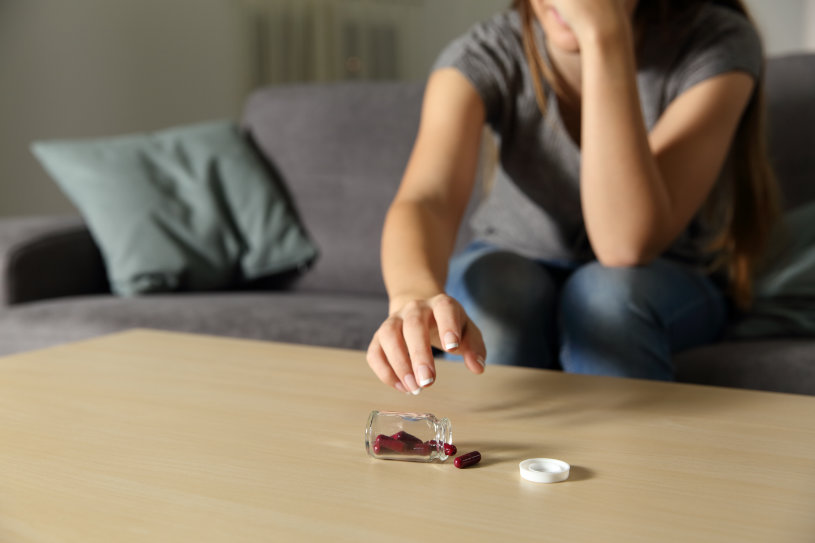 A woman is suffering from Viibryd side effects and has dropped pills on the table.