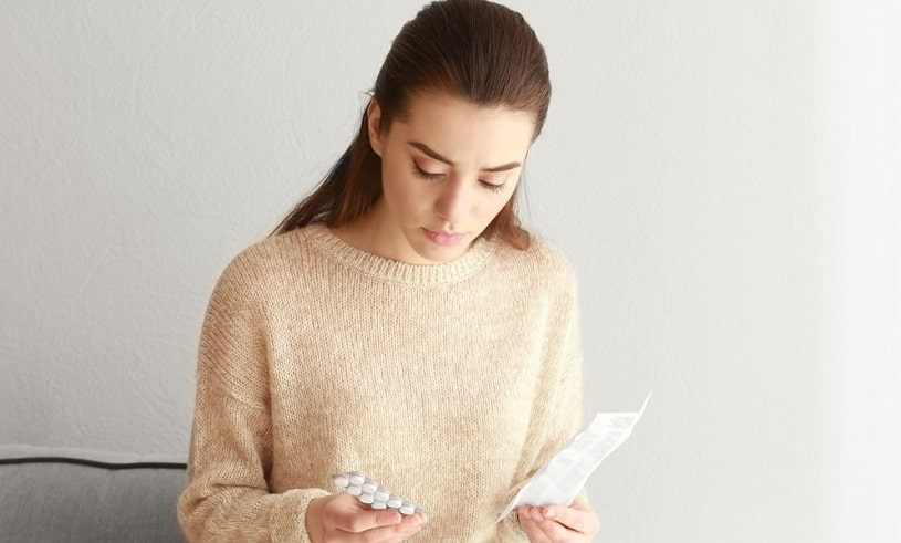 Woman reading Accutane warnings and indications.