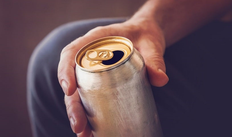 Man holding an energy drink in hand.