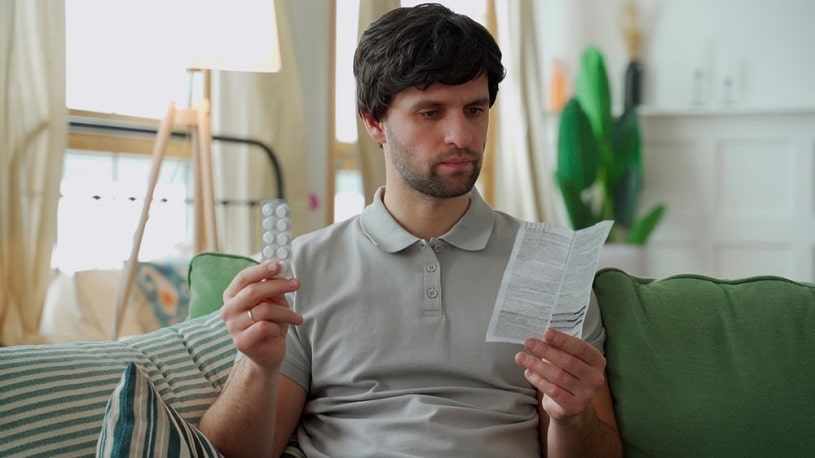 Man with medications reading instruction for Baclofen use.