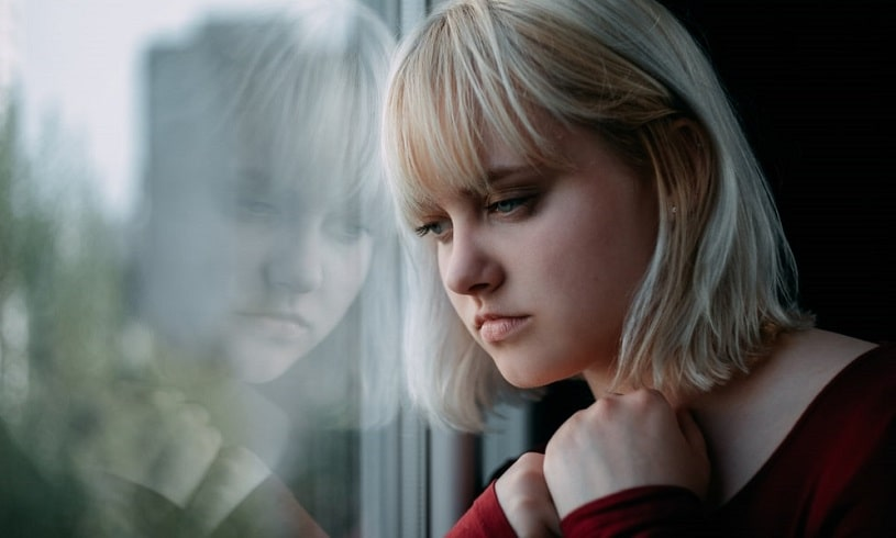 Depressed young woman addicted to methadone looks in the window.