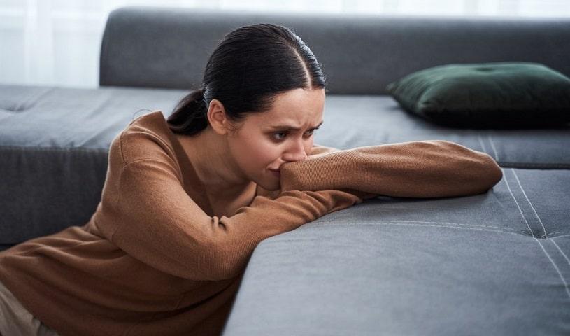 Sad woman experiencing methadone withdrawal at home.