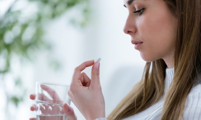 Woman holing a pill and worried about her Lortab abuse.