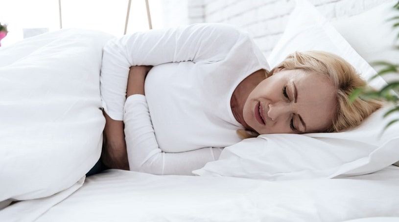 Woman suffering from severe pain lying in bed.
