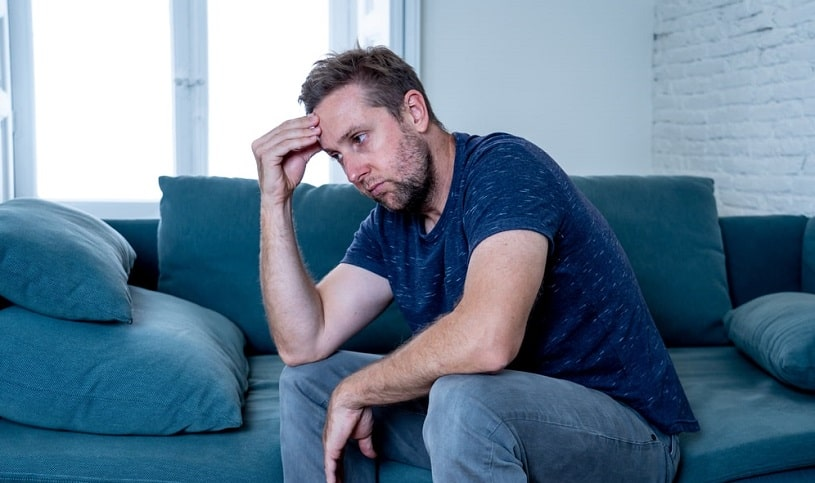 Unhappy depressed man sitting on the couch.
