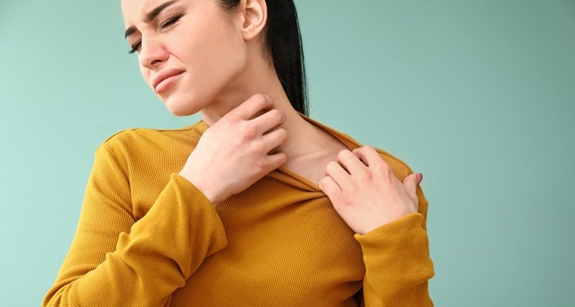Woman experiencing dilaudid allergy, scratching her neck.