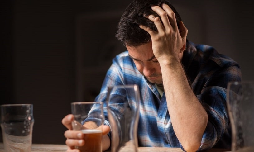 Man sitting at a table suffering from alcoholism.