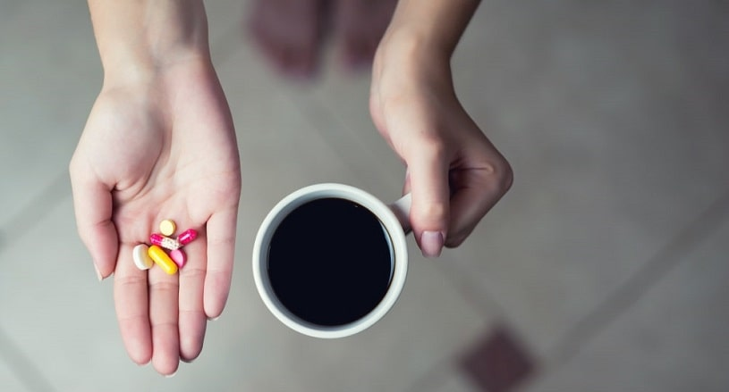 Woman holding coffee cup and caffeine supplements in hand.