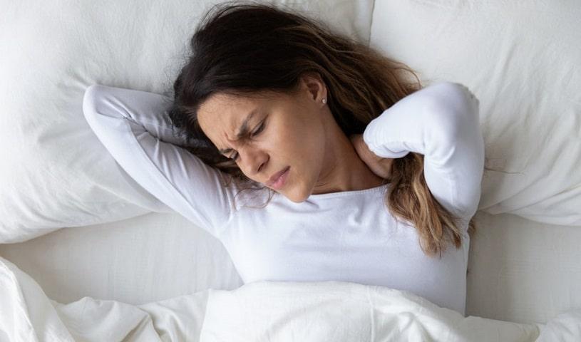 Woman lying in bed feeling muscle pain.