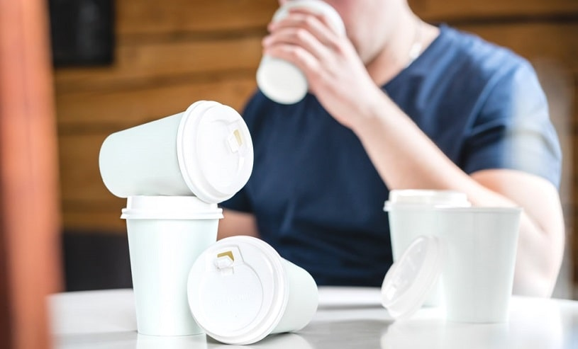 Man sitting at a table with many cups of coffee.