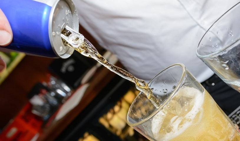 Energy drink being poured into a glass with alcohol.