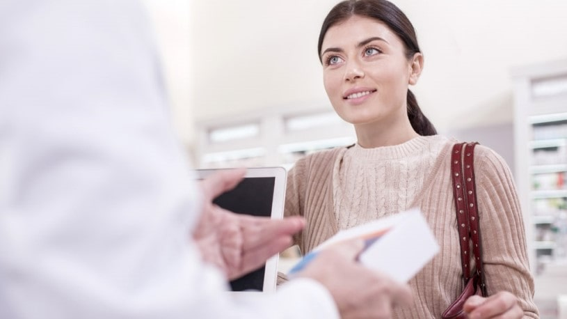 Pharmacist telling a woman about Lortab side effects and precautions.