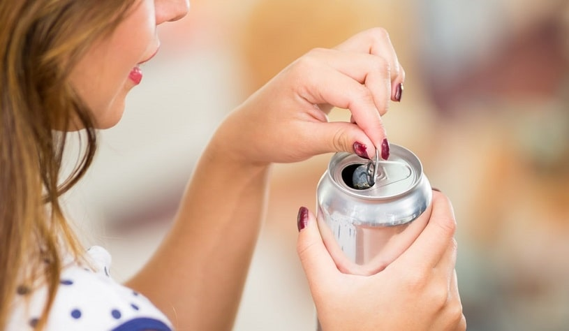 Girl opening a can of caffeinated drink.