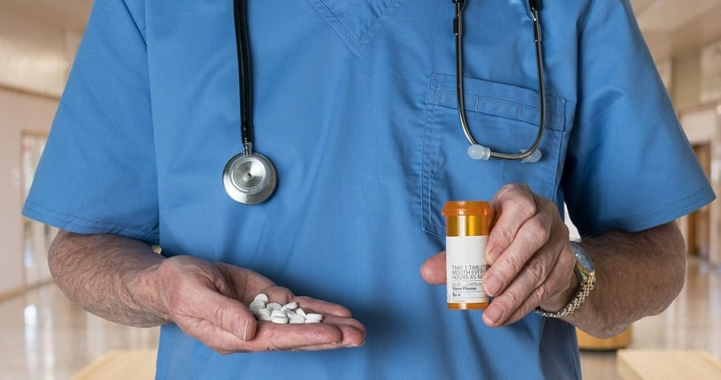 Male doctor holding dilaudid pills in the bottle.