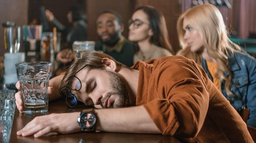 Drunk man sleeping at a bar.