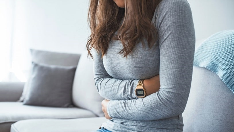 Woman on the sofa experiences constipation during caffeine withdrawal.
