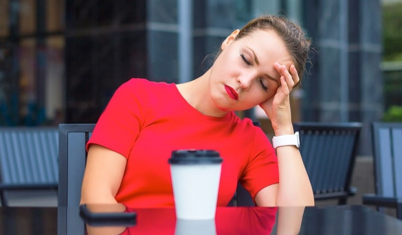 Woman experiencing caffeine headache sitting at the table.