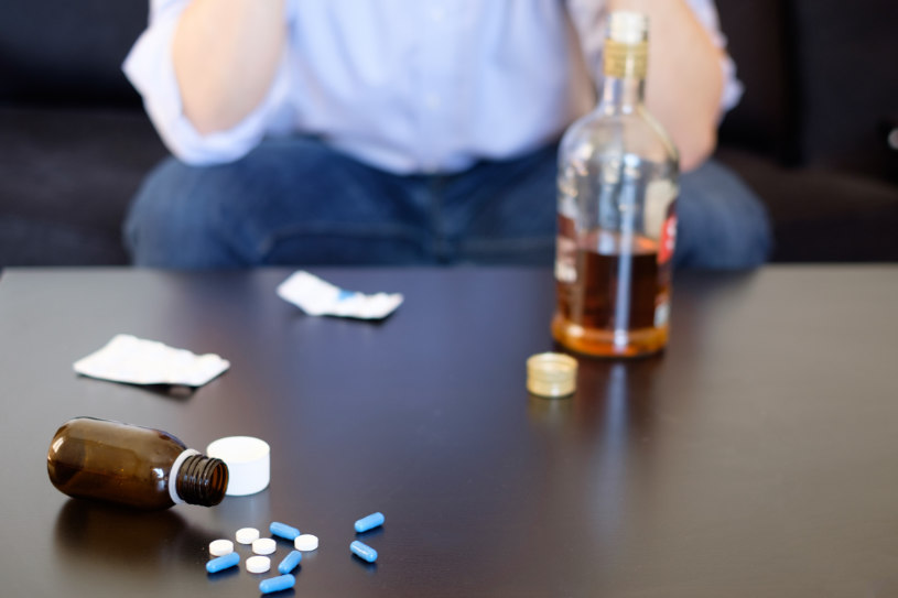 A bottle of alcohol and Amitriptyline pills are on the table.
