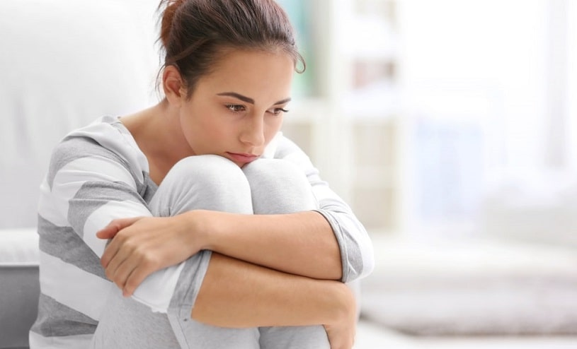 Depressed sad woman sitting on the couch.