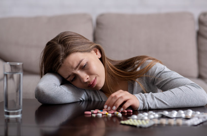 Depressed woman sit on the groud and watches on pills.