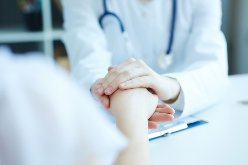 Friendly female doctor's hands holding female patient's hand for encouragement and empathy.