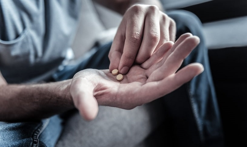 Man holding two pills in hand, is going to take them.