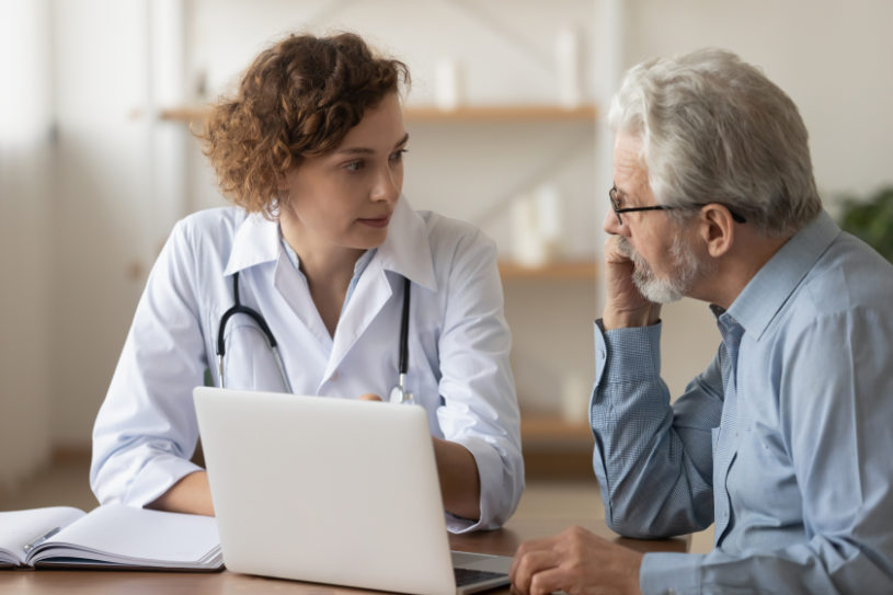 Young female professional doctor physician consulting old male patient.