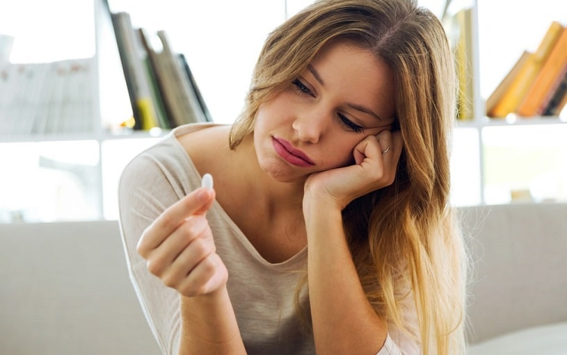 Depressed young woman during Halcion withdrawal holding a pill.