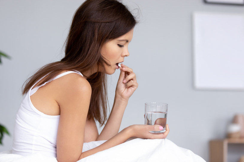 young girl holding Celexa pill and glass of water.