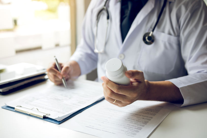 A doctor man holding a pill bottle and writing while talking with a patient and reviewing his medication at office room.