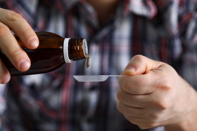 A man pours DXM cough syrup into a spoon.
