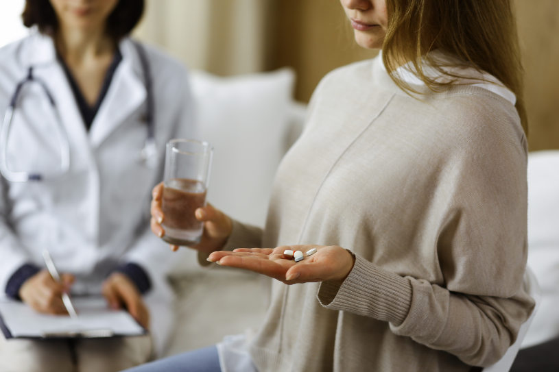 A woman holds a glass of water and DXM pills in her hand.