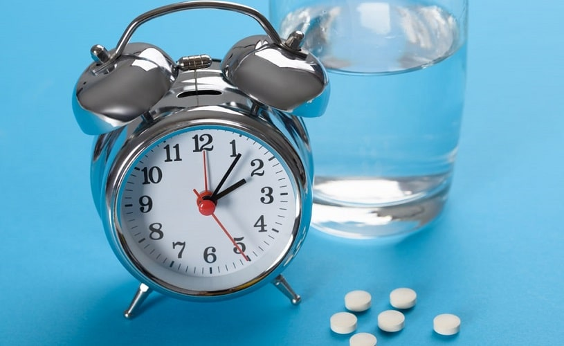 Alarm clock, Ritalin pills and a glass of water on blue background.