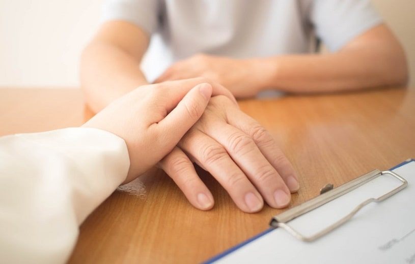 Doctor holding a patient's hand, supporting in Ritalin treatment.