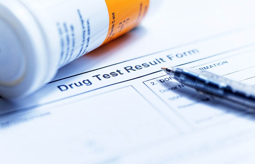 A paper with an imprint drug test and a pen.