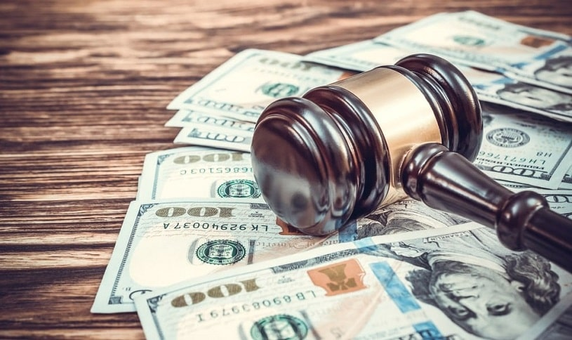 Judge's gavel with dollar bills, fine paid.