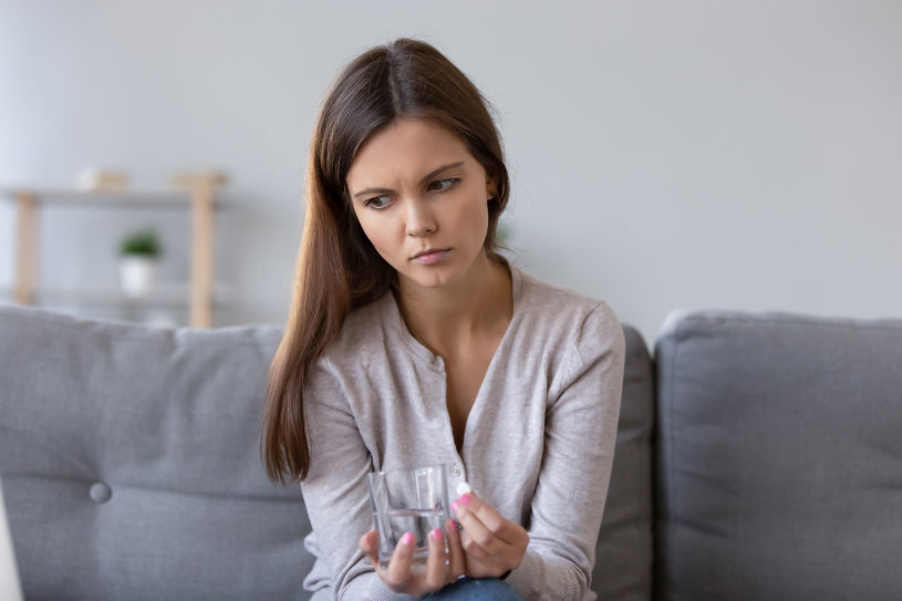 Lonely sad young woman sitting on sofa at home holding pill glass of water.