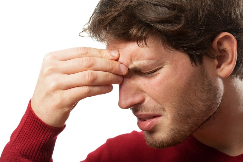 Man holding his forehead because of a headache.