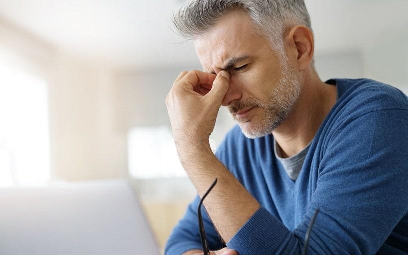 Man at home having a tension headache.