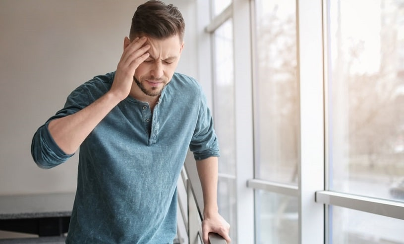 Man experiencing Concerta headache at the office.