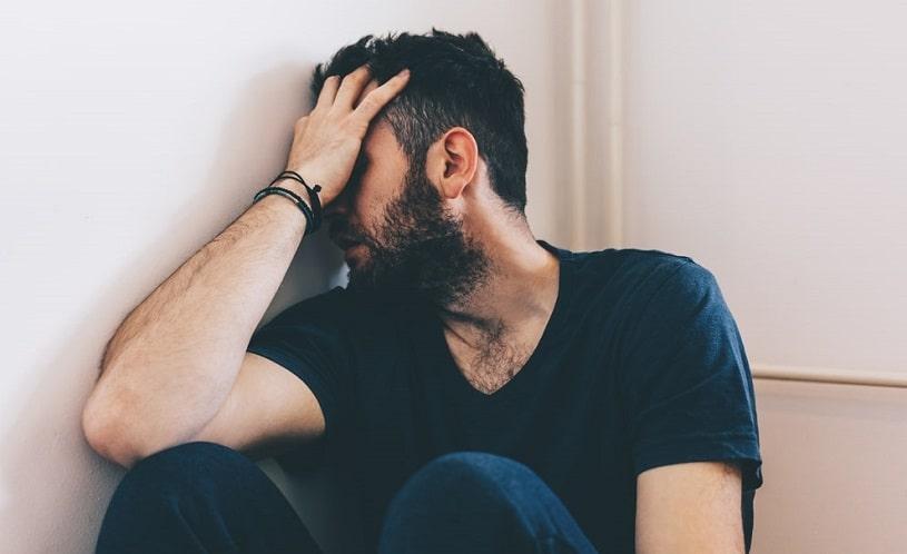 Sad depressed man sitting in the corner.
