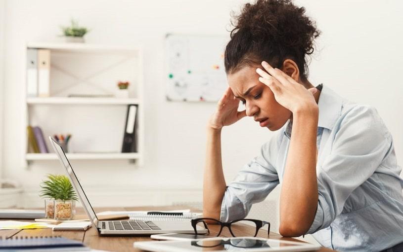Woman has a headache at the office near laptop.