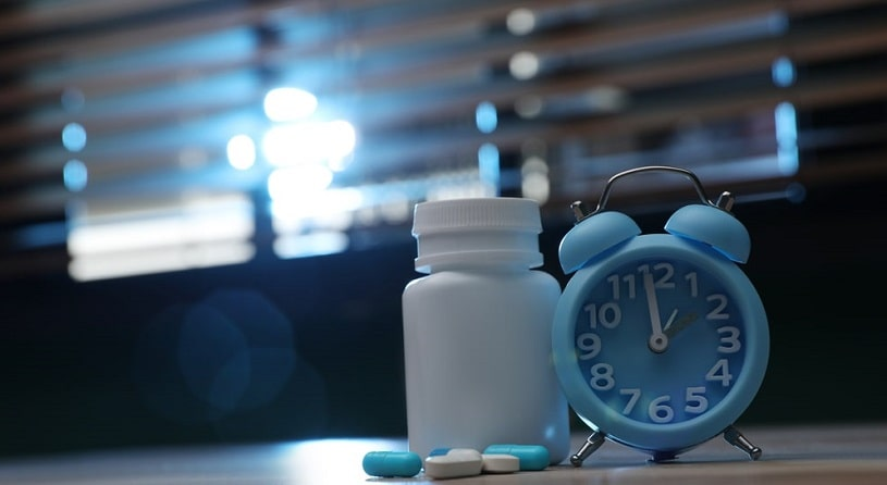 Alarm clock and pills on the table indoors.